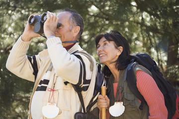 Senior couple looking through binoculars in woods