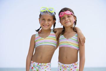 Hispanic sisters wearing matching bathing suits