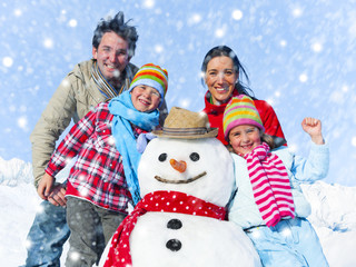 Family Posing With A Snowman Outdoors
