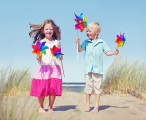Children Playing Pinwheels by the Coastline