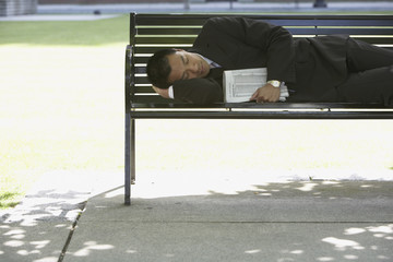 Asian businessman sleeping on park bench