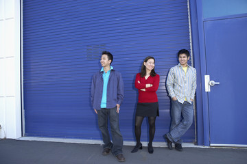 Three friends standing on sidewalk
