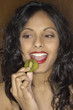 Portrait of Middle Eastern woman eating kiwi slice