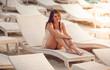 brunette woman sitting on sunbed on sand beach