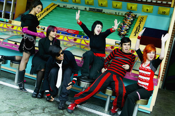Group of punk Hispanic teenagers cheering in carnival booth