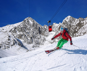 Skier against cable-lift in high mountains