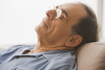 Close up of senior Hispanic man sleeping on sofa