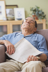 Senior Hispanic man sleeping on sofa