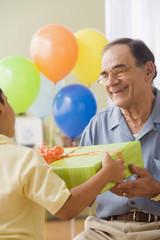 Hispanic grandfather and grandson exchanging birthday gifts