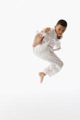 Studio shot of Hispanic boy performing martial arts kick