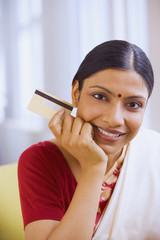 Indian woman in traditional clothing holding credit card