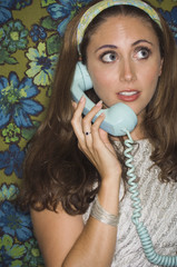 Young woman in retro outfit using telephone