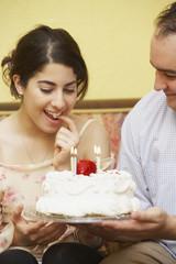 Hispanic man giving girlfriend birthday cake