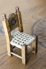 Mini wooden hand made chair on carved table