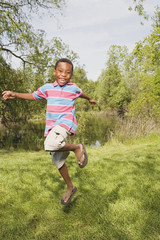 African boy running and jumping in park