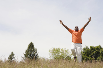 African man running in field with arms outstretched