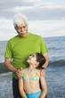 Hispanic grandfather and granddaughter at beach