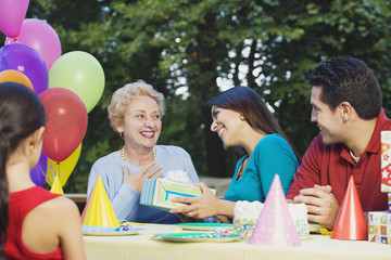Senior Hispanic woman receiving gift at birthday party