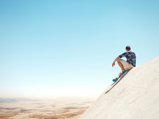 Young man sitting on a peak and desert
