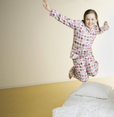 Portrait of girl jumping on bed