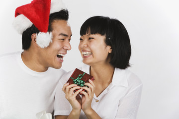 Asian couple laughing and holding gift