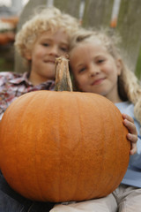Brother and sister holding pumpkin