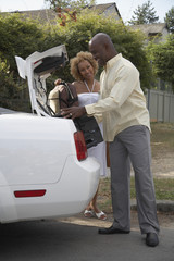 African couple loading luggage into car