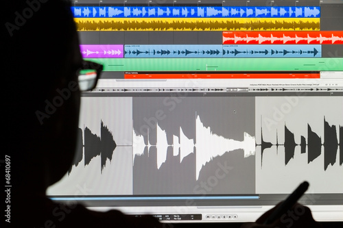 Leinwandbild Motiv Man Editing Digital Audio on a Computer