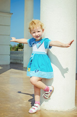 beautiful little smiling girl preschooler posing outdoors in sum