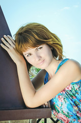 Beautiful young girl on background of blue sky. happy redhead wo
