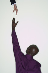 African businessman reaching up for hand