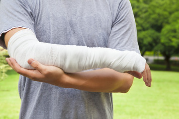 closeup of bandaged arm  with park background