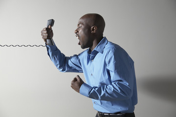 African businessman yelling into telephone