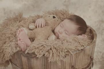 Baby mit Teddy schläft