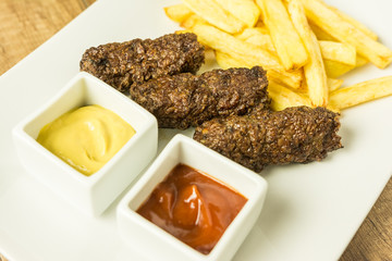 Traditional Romanian Mici And Fries With Ketchup And Mustard