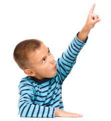 Little boy is pointing up using his index finger