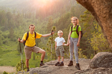 Father and two children with backpacks on beautiful nature