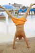 Man performing handstand next to swimming pool
