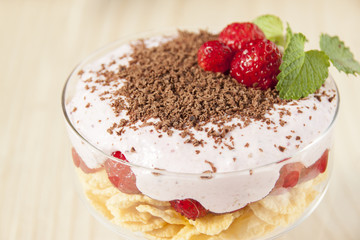 Dessert with curd cream, cereal, strawberries and chocolate.