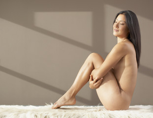Nude Asian woman pulling knees up to chest