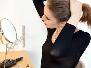 Frau richtet Frisur vor Schminkspiegel