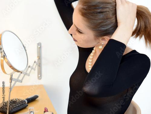 canvas print picture Frau richtet Frisur vor Schminkspiegel