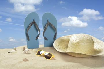 Escena de playa con chanclas, sombrero y gafas