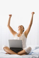 Woman cheering on bed with laptop