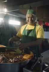 Hispanic man cooking at taco stand
