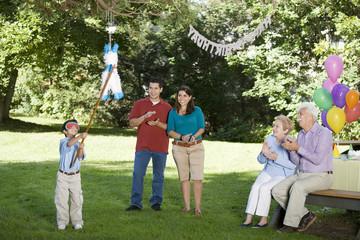Family watching Hispanic boy hitting pinata at birthday party