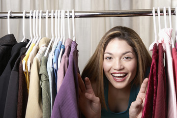 Hispanic woman looking through rack of clothing