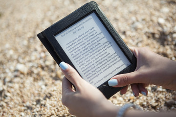 reading ebook reader on a beach