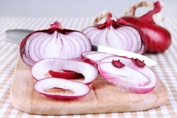 Fresh red onions on cutting board close up