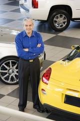 Hispanic car salesman next to new cars